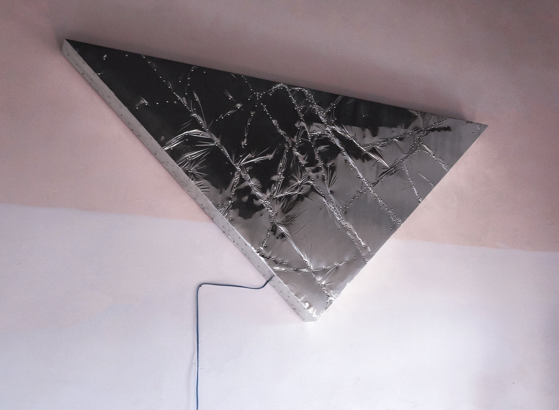 Triangle #1, 2020 | silver reflective mylar film, aluminum pins and plywood, subwoofer, amplifier. 240 × 170 × 170 cm